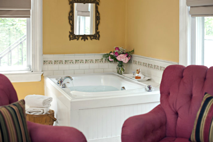 Large soaking tub facing two red wingback chairs