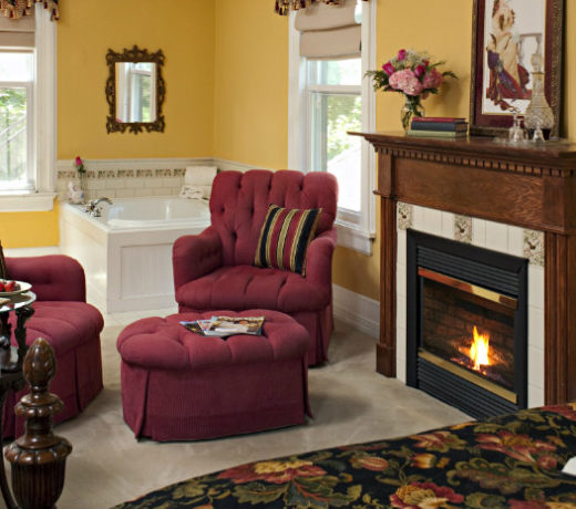 Two red chairs in front of wooden mante fireplace in gold walled room