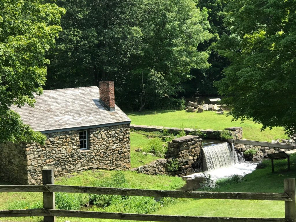 Old stone building with small waterfall into Morris Canal at Waterloo Village Historic Site.