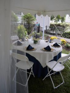 A table with white linens under a romantic tent on the garden property of Whistling Swan Inn.
