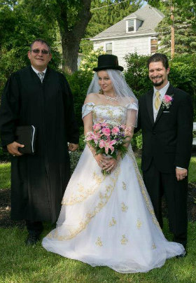 Bride and groom with black robed officiant in the garden