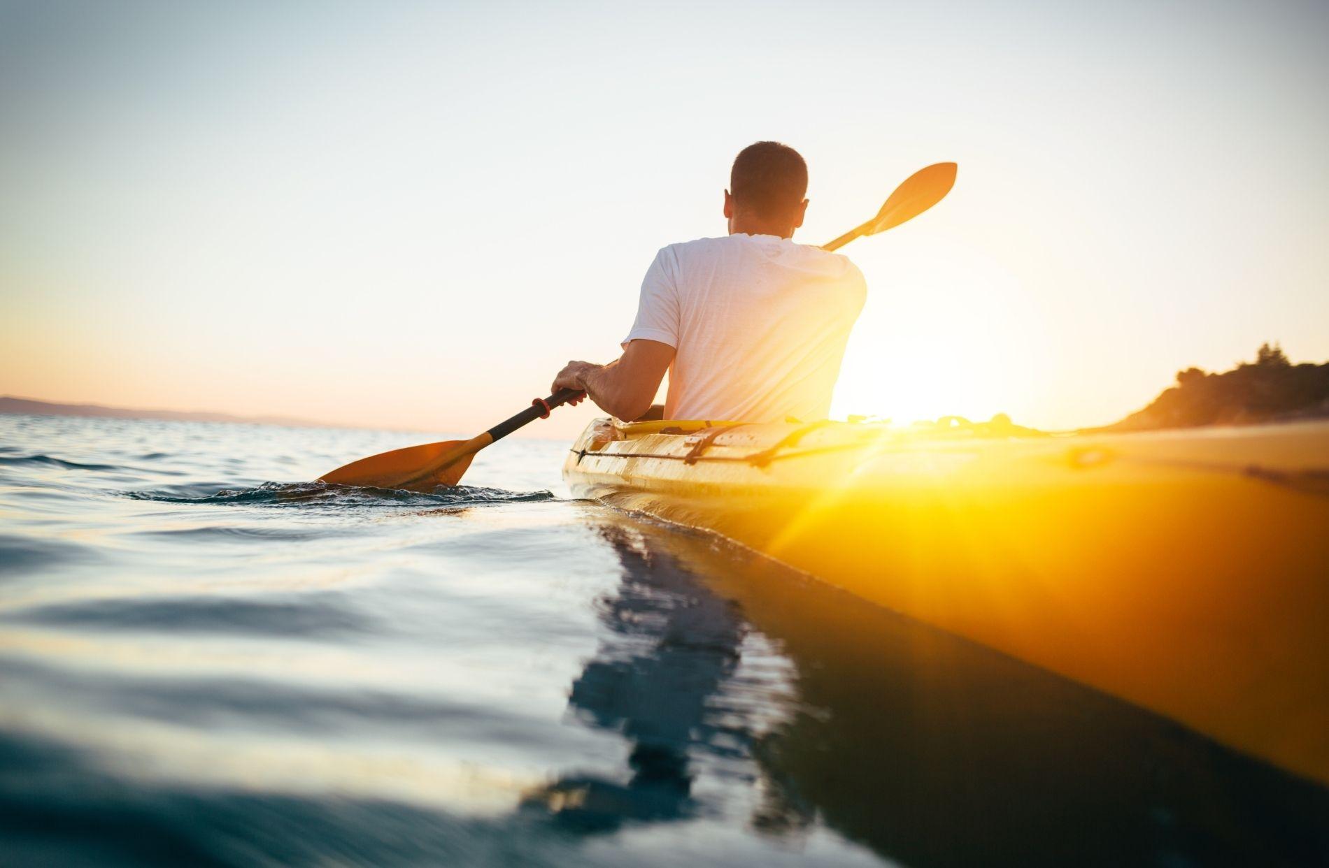 Man in white t-shirt paddling a yellow kayak as the sun sets